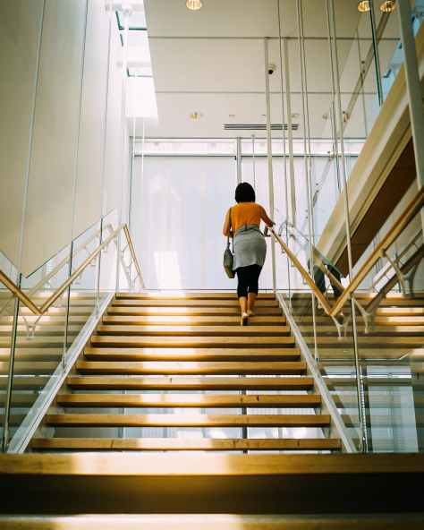 woman walking on brown stair
