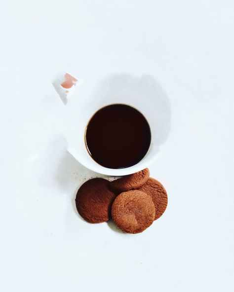 four cookies near white ceramic mug
