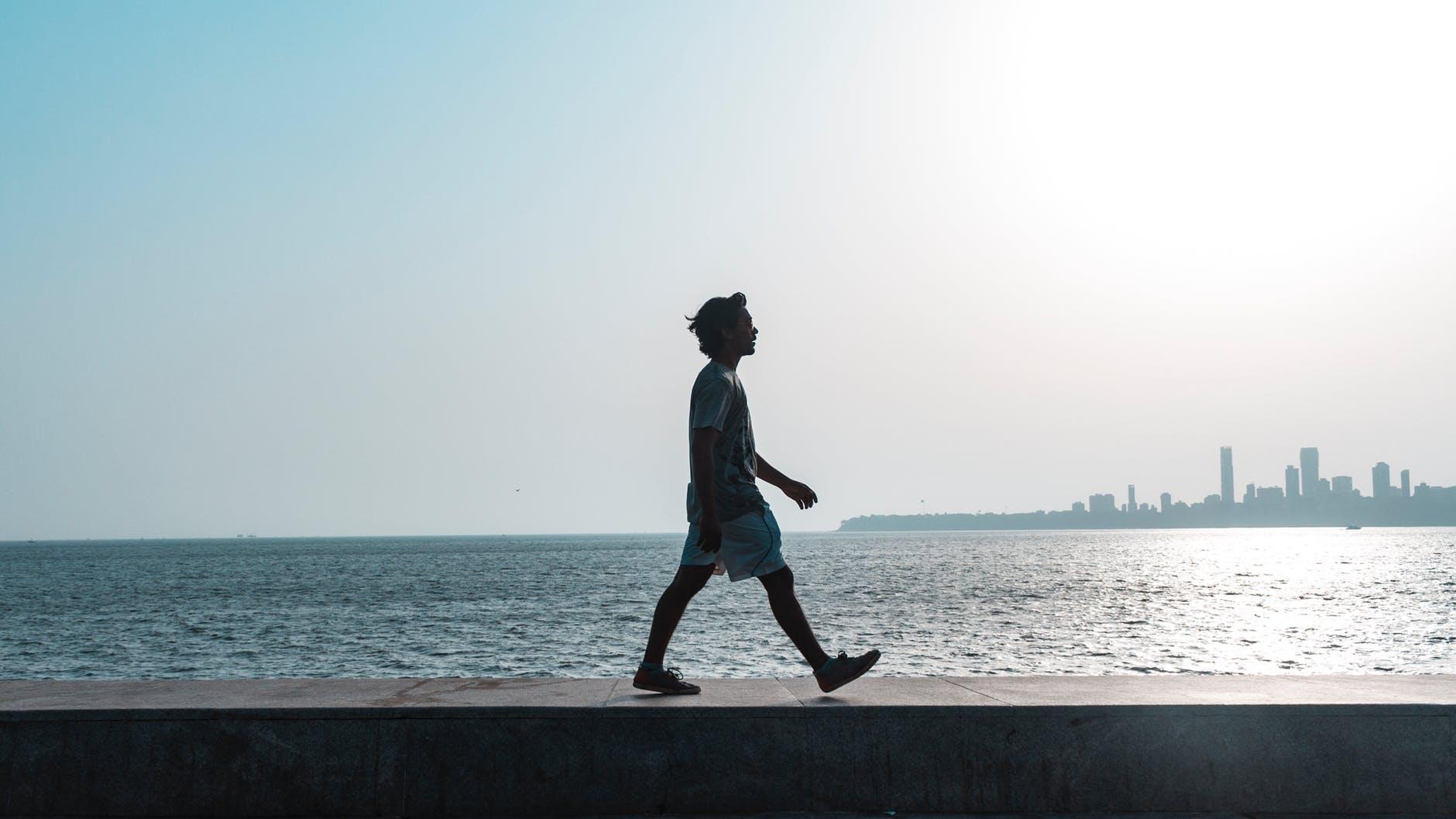 man walking near body of water