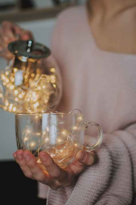 person holding clear glass mug filled with mini string lights