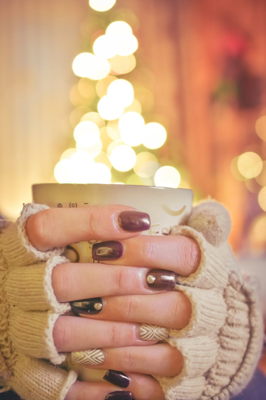 person holding a mug infront of a lighted christmas tree