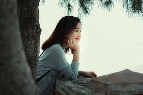 photo of smiling woman standing near tree leaning on stone railing looking out into the distance