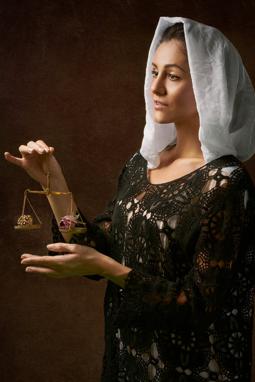 woman in black dress holding balance scale