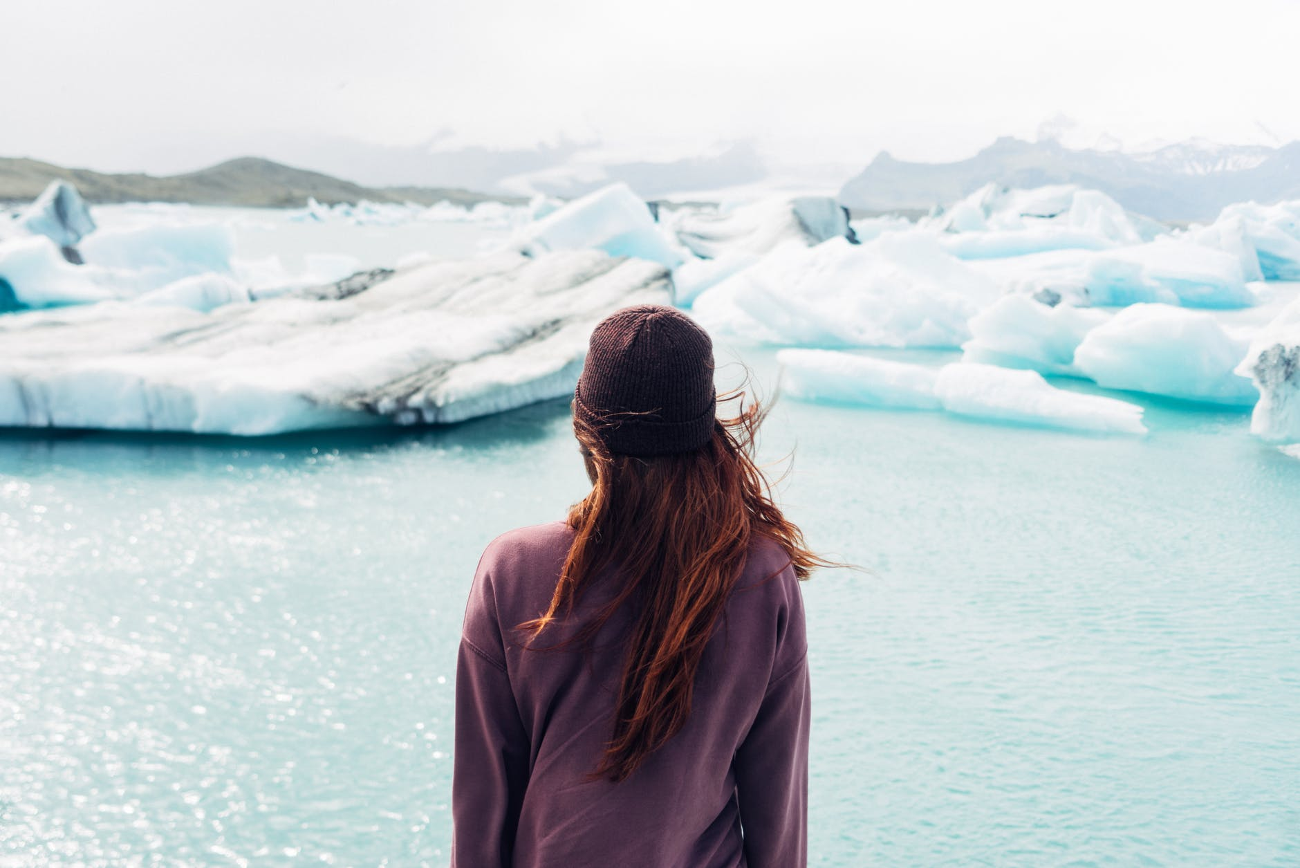 woman wearing purple shirt overlooking at body of water and snow covered field