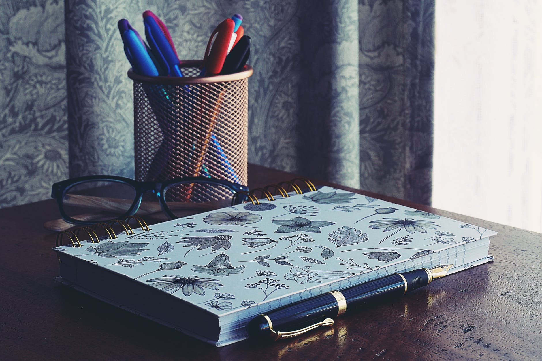 close up photography of notebook near pens