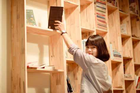 woman standing beside book shelf