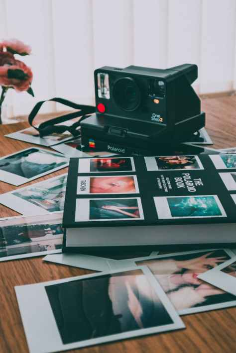 photo of polaroid camera near book