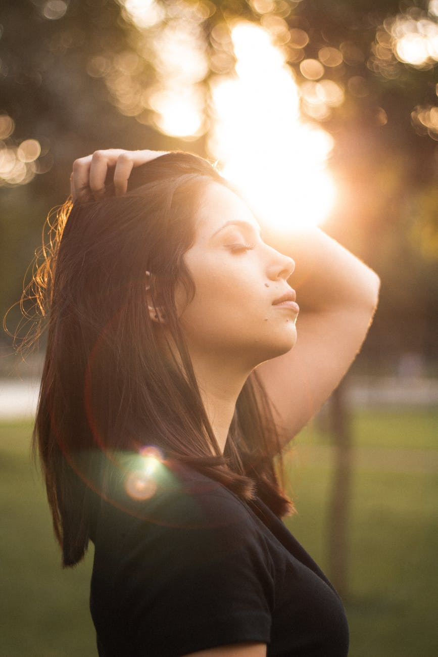 side view photo of woman with her eyes closed holding her her as sunlight shines on her face