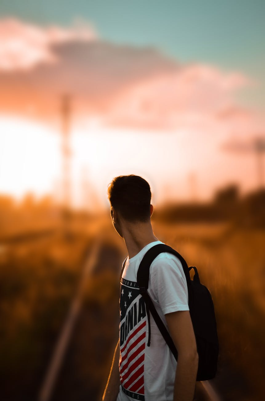 selective focus photography of a man in white printed t shirt carrying backpack