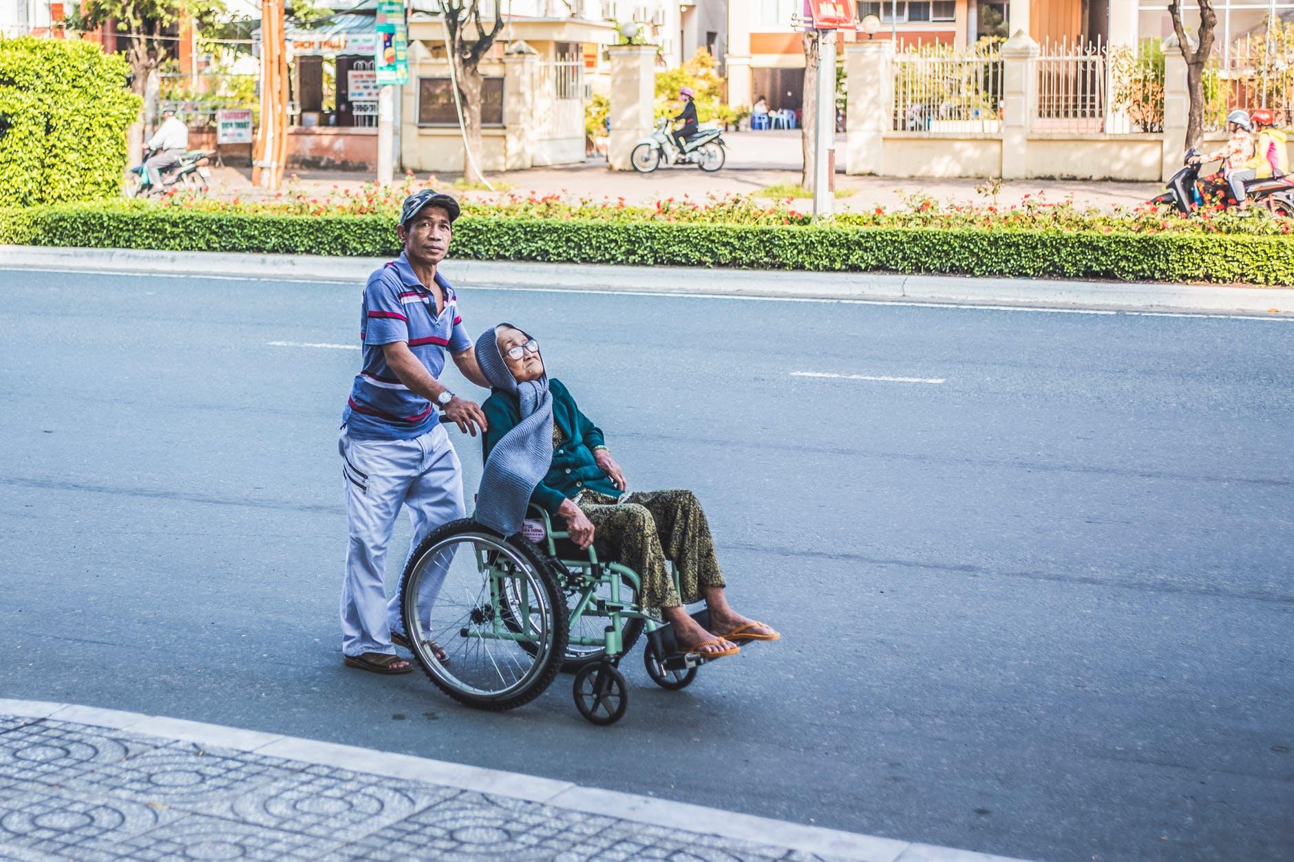 man pushing a woman sitting on wheelchair
