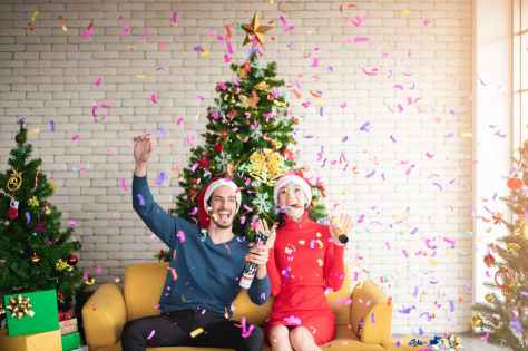 man and woman wearing santa hats sitting on sofa popping a confetti surrounded by christmas trees