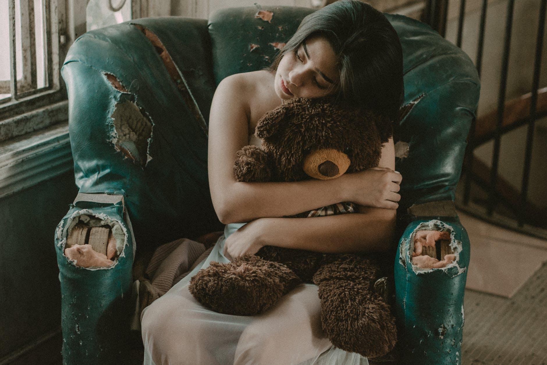 woman hugging brown bear plush toy