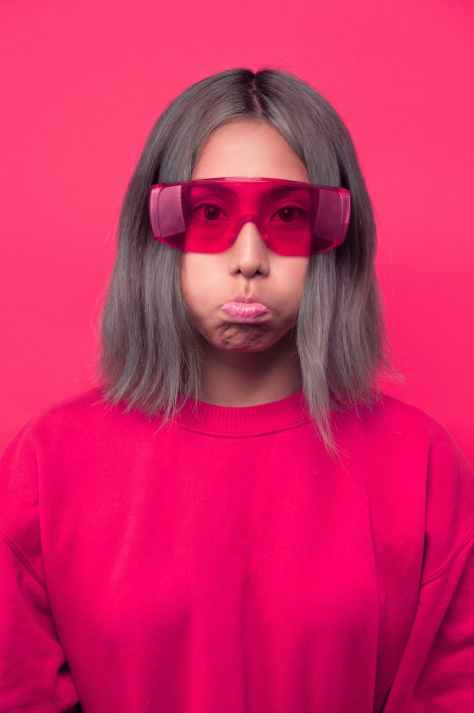 frowning woman wearing pink shirt and sunglasses