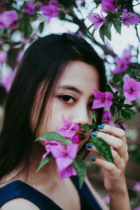 woman holding purple petaled flower