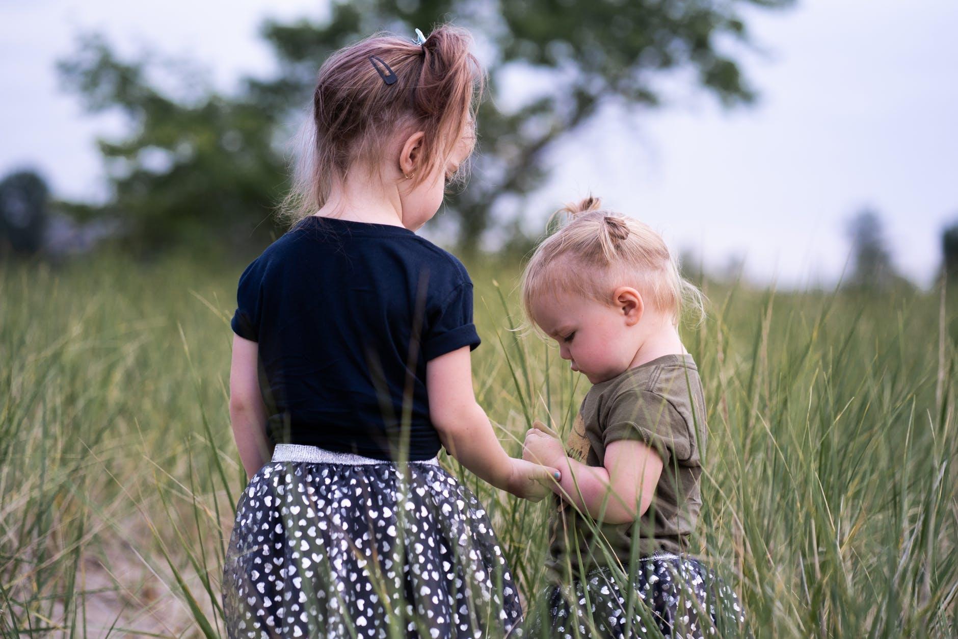 two girls standing on grass field