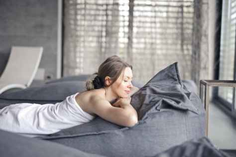 woman in white tank top lying on gray bed