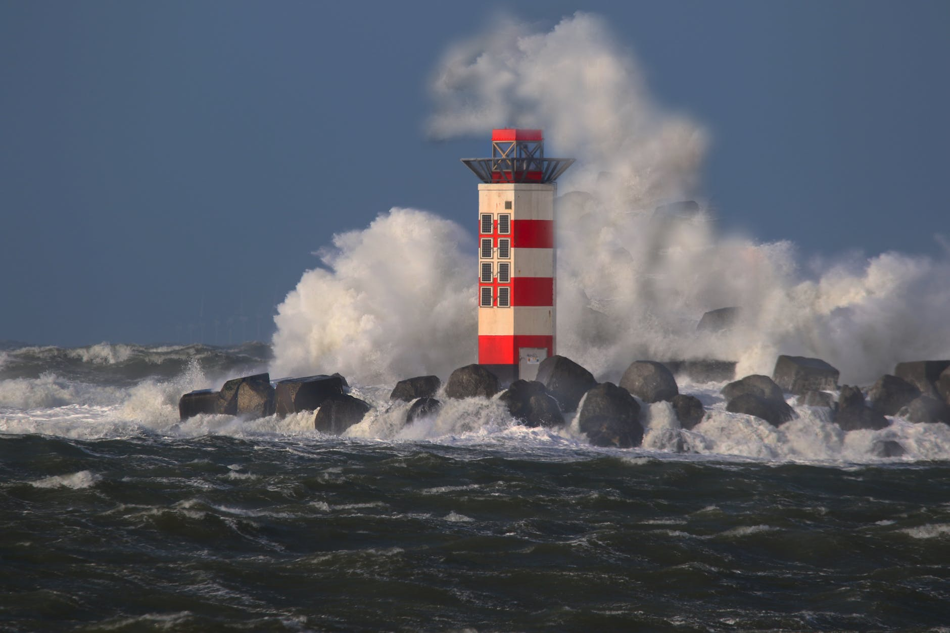 white and red lighthouse on rocky shore
